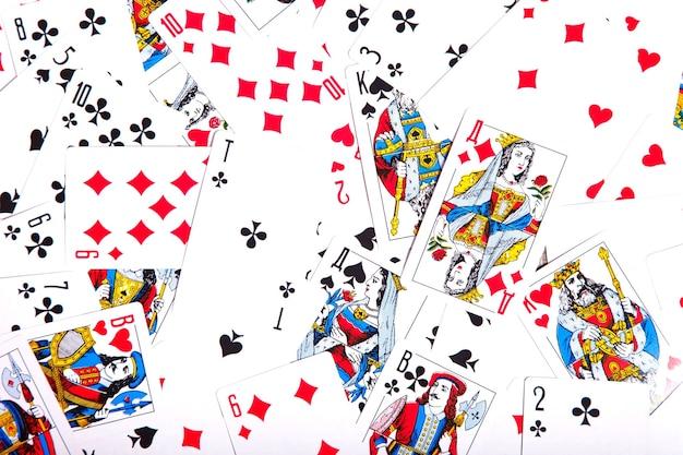 На столе разбросаны игральные карты. фон из разбросанной колоды карт, заполняющей все пространство изображения. вид сверху, крупный план. место под авторское право для сайта или логотипа