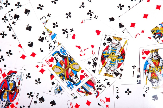 На столе разбросаны игральные карты. фон из разрозненной колоды карт, заполняющей все пространство изображения. вид сверху, крупный план. место под авторское право для сайта или логотипа