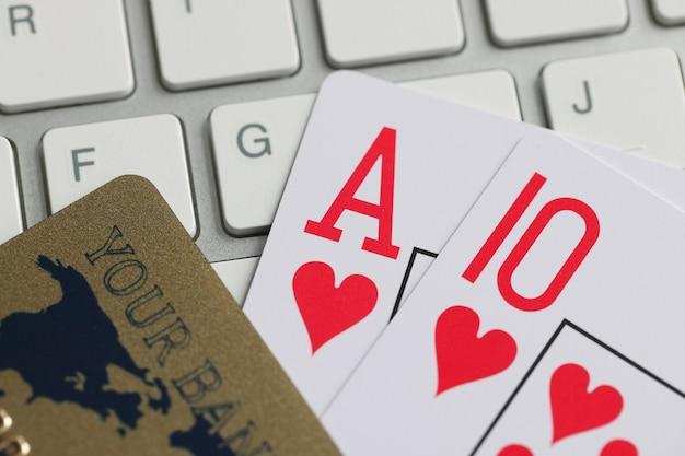 トランプ銀行のクレジットカードとテーブルのオンラインギャンブルの概念上のコンピューターのキーボード