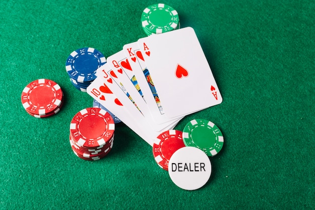 Playing cards and casino chips on green surface