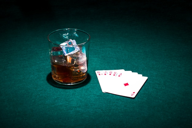 Playing cards and glass of whiskey on green table