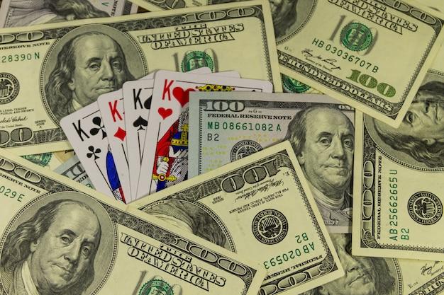 Игральные карты на фоне американских сто долларовых купюр. концепция игры