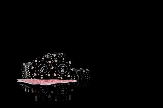 Playing cards and poker chips on black background