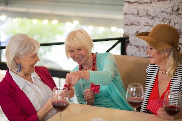 카드 놀이. 카드 놀이를 하고 즐거워 보이는 수석 잘 생긴 쾌활한 여성