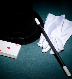 Playing cards; white gloves; top hat and magic wand on green background