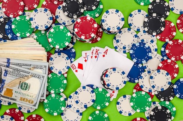 緑の布にチップとお金でトランプ