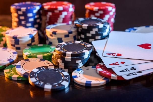 黒の背景でポーカーチップとトランプ