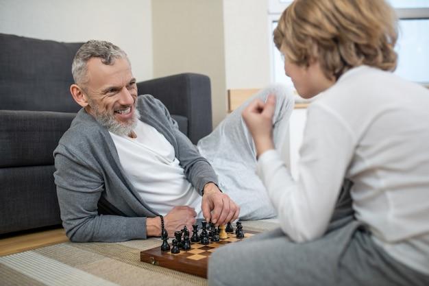 チェスをしている。父と息子がチェスをし、関与しているように見える