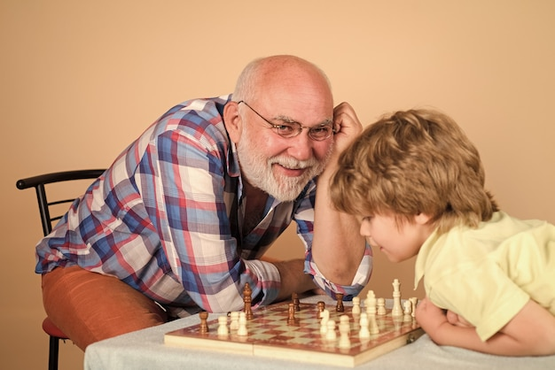 Playing chess kid playing chess with grandpa grandfather and grandson play chess family activities