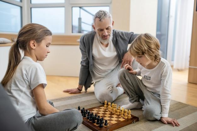 チェスをしている。父親が見ている間にチェスをしている兄弟