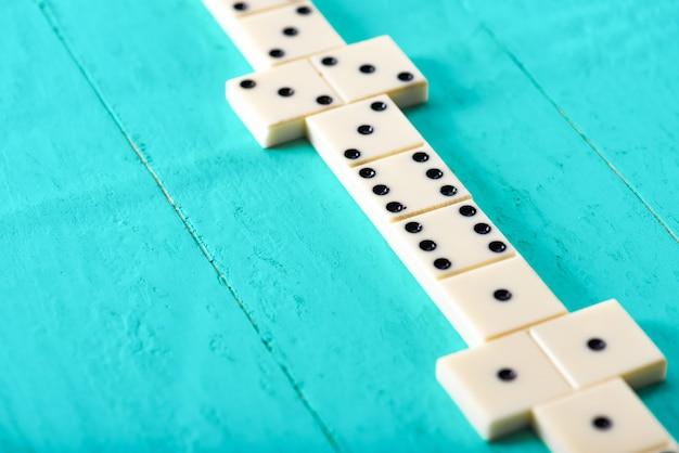 Игра в домино на синем деревянном столе
