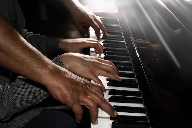 Playing four male hands on the piano. palms lie on the keys and play the keyboard instrument in a music school. student learns to play. hands of a pianist. black dark background.