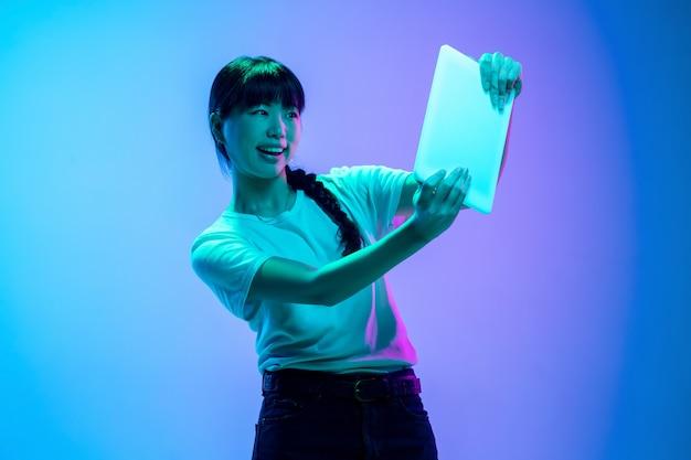 태블릿에서 게임하기. 네온 불빛에 그라데이션 파란색 보라색 스튜디오 배경에 젊은 아시아 여성의 초상화. 젊음, 인간의 감정, 표정, 판매, 광고의 개념. 아름 다운 갈색 머리 모델입니다.