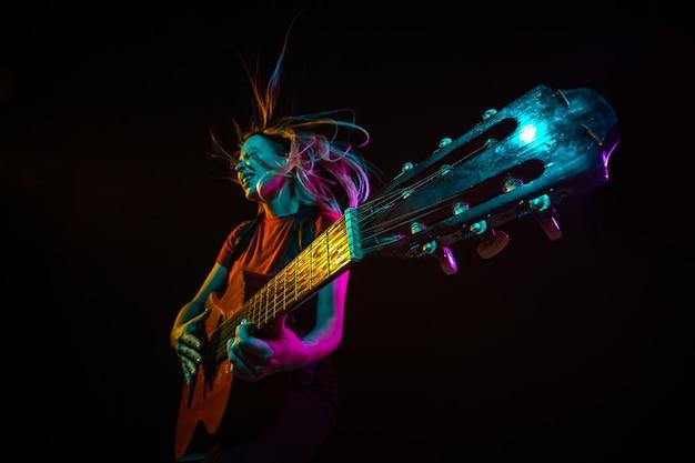 Играть на гитаре. молодая женщина с дымом и неоновым светом на черном фоне. сильно натянутый, широкий угол обзора, рыбий глаз. понятие человеческих эмоций, выражения лица, продаж, рекламы, спорта.
