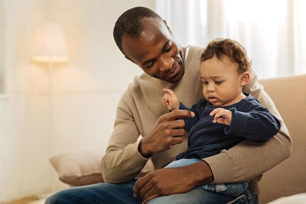 遊んでいます。幸せな黒髪のアフリカ系アメリカ人の男が彼を抱きしめながら笑顔で子供と遊んでいます