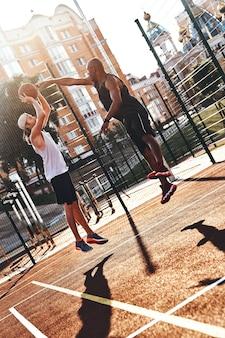 열심히 연주합니다. 야외에서 시간을 보내는 동안 농구를하는 스포츠 의류에 두 젊은 남자