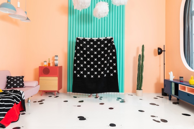 Playing hide-and-seek and having fun using plaid at home while self-isolation in a bedroom with colorful accents and geometrically-patterned textile.