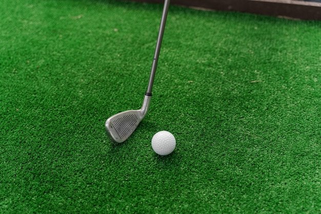 Playing in mini-golf on the green grass using niblick