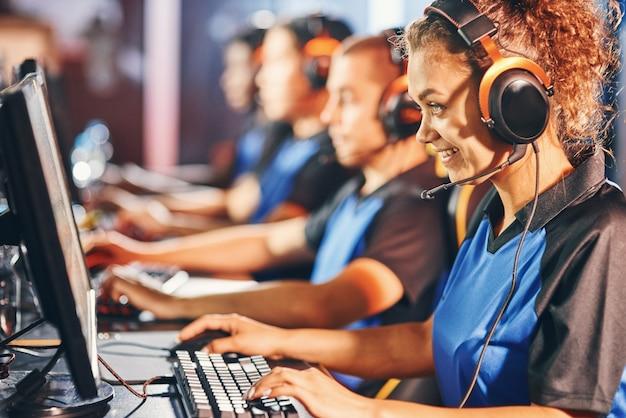 オンラインビデオゲームをプロとしてプレイする。幸せな混血の女の子、チームと一列に座って、eスポーツトーナメントに参加しているヘッドフォンを身に着けている女性のサイバースポーツゲーマーの側面図