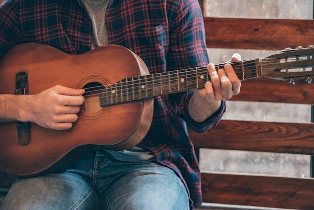 完璧なコードを演奏します。窓辺に座ってギターを弾く若い男のクローズアップ部分