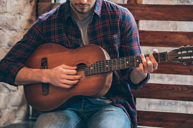 完璧なリフを演奏します。窓辺に座ってギターを弾く若い男のクローズアップ部分