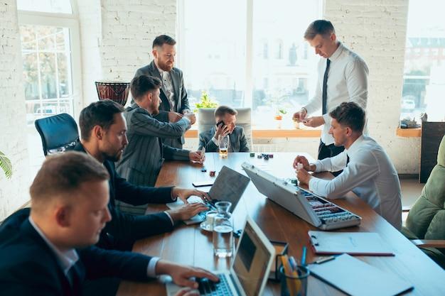 Игра в покер, азартные игры на рабочем месте. счастливые беззаботные коллеги веселятся в офисе, в то время как их коллеги усердно и сосредоточенно работают. понятие о развлечениях, отдыхе, профессиональном занятии.