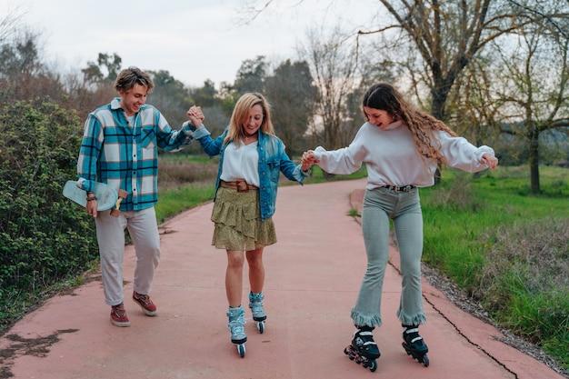 Занятия спортом всей семьей. сын на коньках, сестра на роликовых коньках и мама на велосипеде.