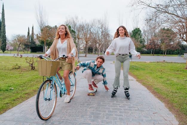 Занимаемся спортом всей семьей во время празднования дня матери. сын на коньках, сестра на роликовых коньках и мама на велосипеде.