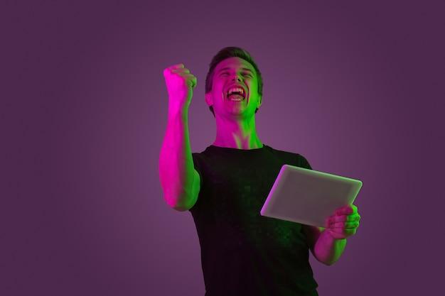 タブレット、ビデオゲーム、勝利。ネオンの光の紫色のスタジオの背景に白人男性の肖像画。黒のシャツを着た美しい男性モデル。人間の感情、顔の表情、販売、広告の概念。