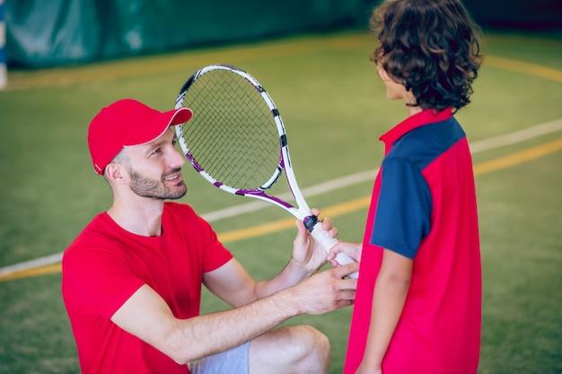 테니스. 빨간 모자를 쓴 코치와 테니스 라켓을 든 소년