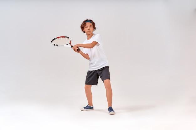 テニスラケットを持って孤立して目をそらしている10代の少年のテニスのフルレングスのショットを再生します