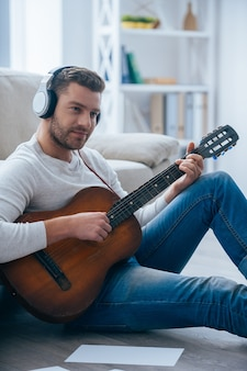 Playing that melody. handsome young man in headphones playing guitar
