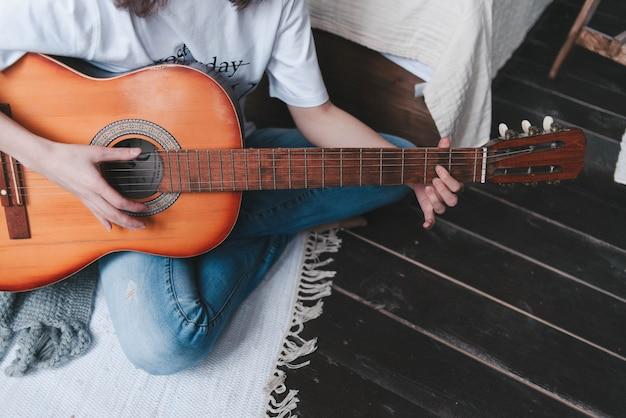 클로즈업에서 기타를 연주. 소녀는 기타를 들고있다. 손에 나무 기타입니다.