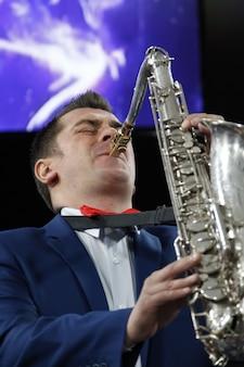 Играет на саксофоне. профессия музыканта. саксофонист. исполнять джаз