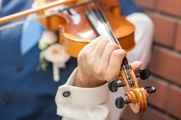バイオリンを弾く。演奏者の手による楽器