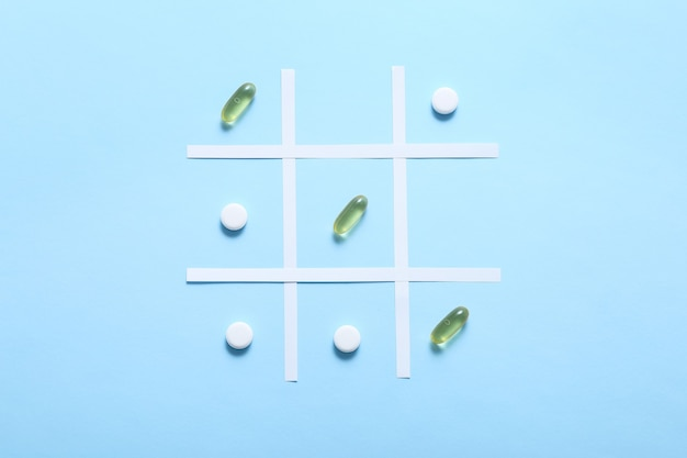 Playing tic tac toe with pills on blue