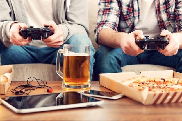 ビデオゲームをプレイ。ソファに座ってビデオゲームをプレイしている2人の男性のクローズアップ