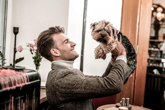 개와 놀기. 그의 손에 작은 개를 들고 남자