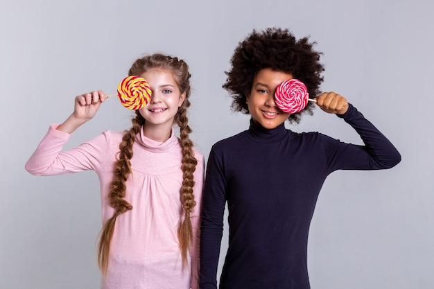 Playing with candies. smiling beaming kids wearing turtlenecks while making photos and holding colorful candies in front of faces
