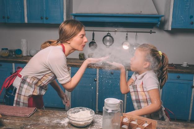 小麦粉で遊ぶ。自家製ケーキを調理しています。幸せな愛情のある家族が一緒にパン屋を準備しています。母と子の娘の女の子はクッキーを調理し、キッチンで楽しんで