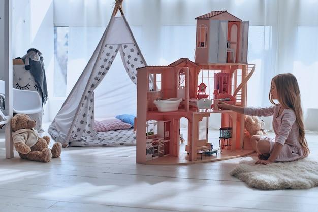 彼女のおもちゃで遊んでいます。寝室の床に座ってドールハウスで遊ぶかわいい女の子