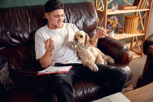 Играем с домашними животными. молодой человек сидит на коричневом диване со своей милой собакой американский кокер-спаниель в помещении. концепция уютной домашней атмосферы, дружбы, удаленного офиса, учебы из дома.