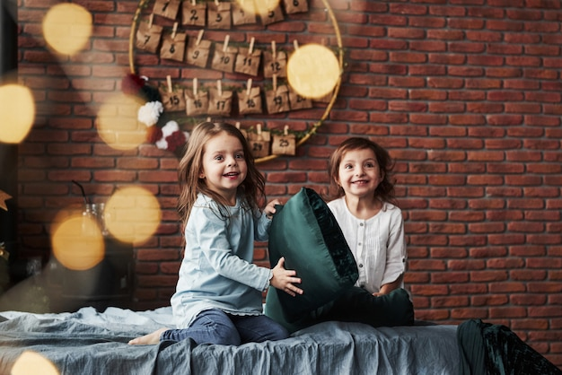 Playing with pillow. little girls having fun on the bed with holiday interior at the background