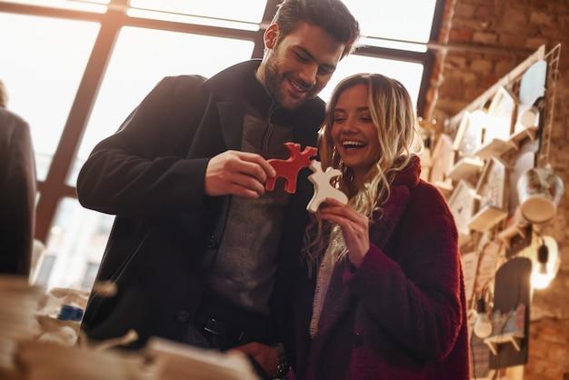 サンタさんの鹿と遊ぶ。小さなストリートマーケットで装飾鹿と遊ぶ幸せな若い楽しいカップル。秋のシーズン、ストリートマーケットで彼女のボーイフレンドと笑っているブロンドの髪の女性
