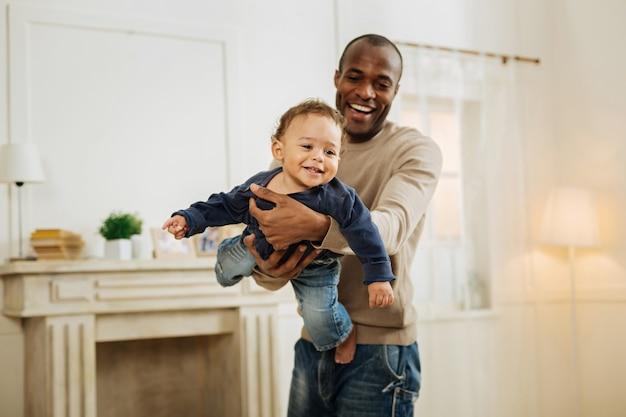 息子と遊ぶ。彼の腕に彼を保持しながら彼の若い笑顔の息子と笑顔で遊んでいる陽気な黒髪のアフリカ系アメリカ人の男