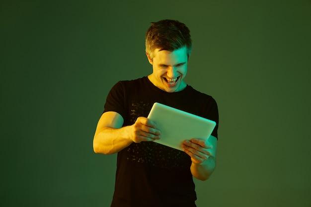 Giocare con il tablet. ritratto di uomo caucasico isolato su sfondo verde in luce al neon.