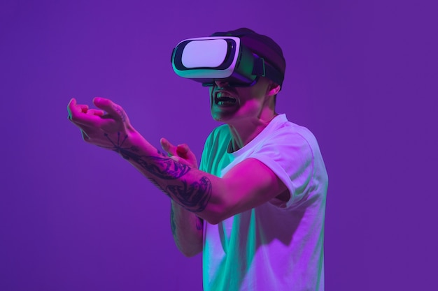 Playing with vr-headset. caucasian man's portrait isolated on purple studio background in pink neon light. beautiful male model in casual. concept of human emotions, facial expression, sales, ad.