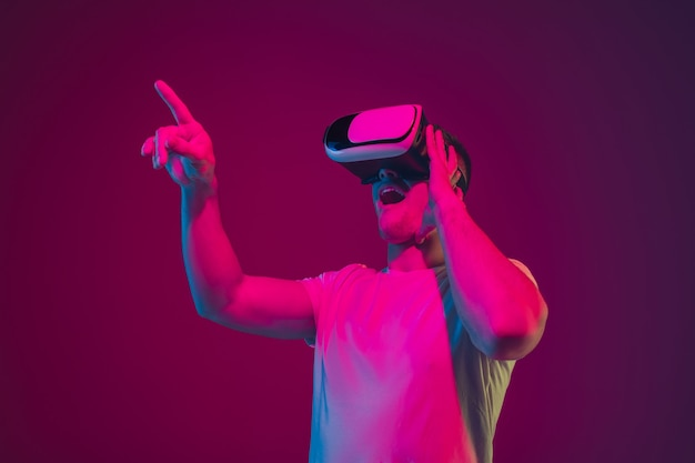Vr로 놀기, 사격, 운전. 분홍색 보라색 스튜디오 벽에 격리된 백인 남자의 초상화.