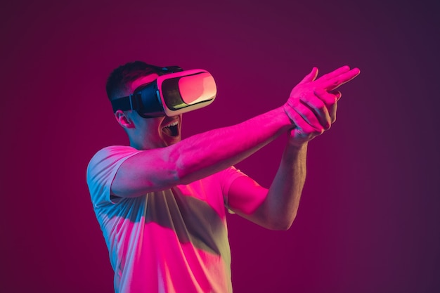 Playing with vr, shoting, driving. caucasian man's portrait isolated on pink-purple  wall in neon light. male model with devices. concept of human emotions, facial expression, sales, ad.