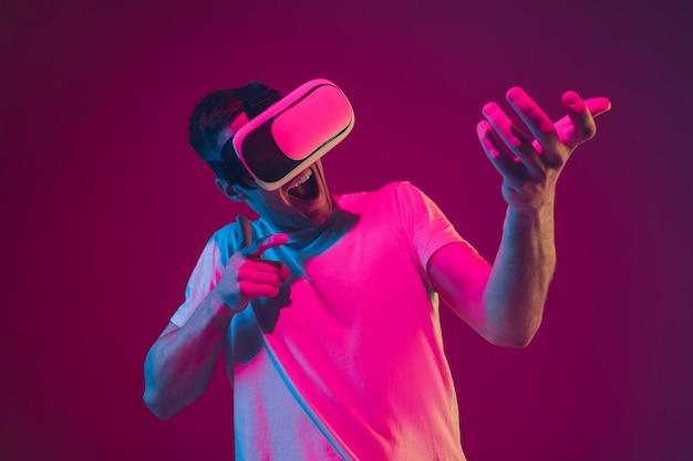 Играем с vr, стреляем, едем. портрет кавказского человека на розово-фиолетовой студии в неоновом свете.